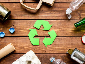 Eco concept with recycling symbol and garbage on wooden table background top view