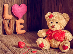 Valentines Day. Teddy Bear Loving with red hearts, Handmade word Love. Vintage. Retro Styled on wooden background